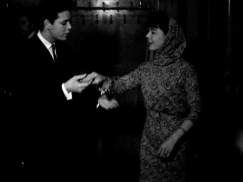 vídeos de stock, filmes e b-roll de cliff richard helps janet munro with her curtsey at the rehearsal for the royal film performance at the odeon theatre 1962 - atriz