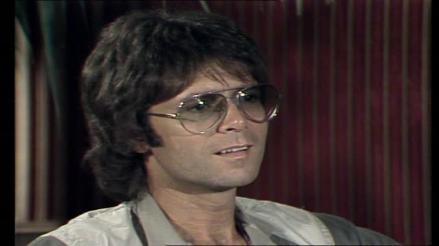cliff richard interview with donnie sutherland in a hotel lounge re producing his own records and on 'wired for sound' - cliff richard stock videos and b-roll footage