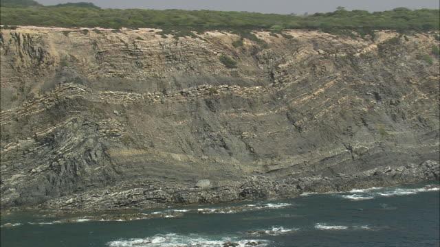 vidéos et rushes de aerial ws cliffs along coast / sines, setubal, portugal - strate géologique