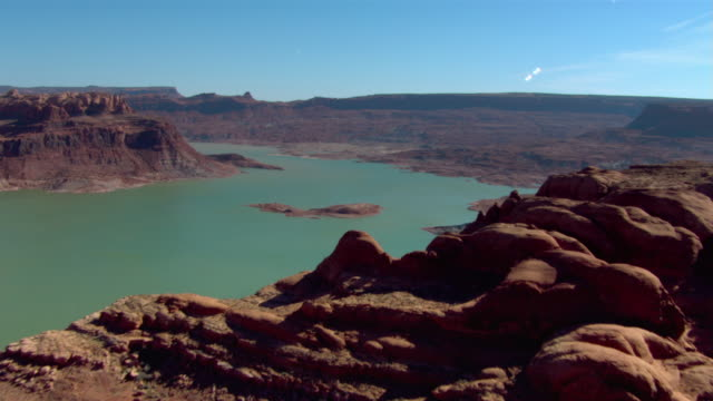 vídeos de stock e filmes b-roll de cliffs and rugged, beautiful buttes surround lake powell. - lago powell