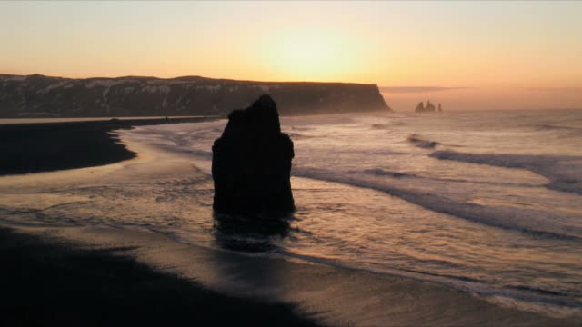 ws cliffs and volcanic rock at water's edge at sunset, dyrholaey near vik, iceland - oceano atlantico del nord video stock e b–roll