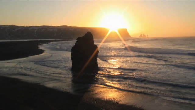 t/l ws cliffs and volcanic rock at water's edge at sunset, dyrholaey near vik, iceland - dyrholaey stock videos & royalty-free footage