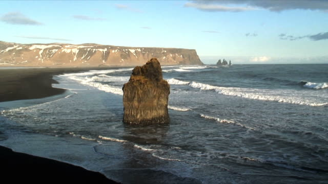 ws cliffs and volcanic rock at water's edge near vik, iceland - oceano atlantico del nord video stock e b–roll