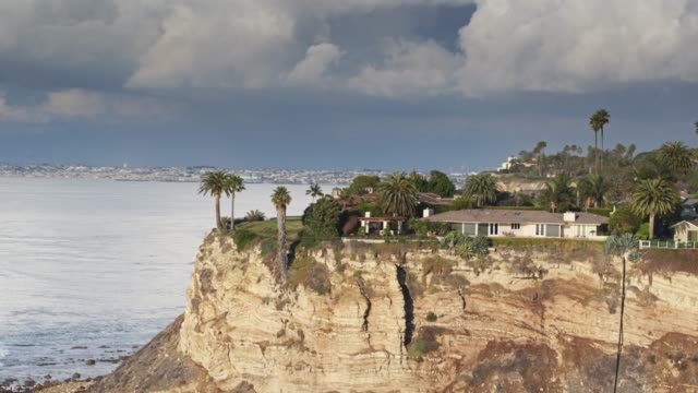 clifftop houses in palos verdes with los angeles visible along coastline - aerial - klippe stock-videos und b-roll-filmmaterial