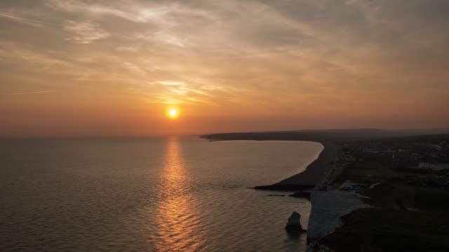 vídeos y material grabado en eventos de stock de a clifftop view as the sun sets through a hazy sky looking across the english channel and seaford beach the sun sets behind brighton in the far distance - east sussex