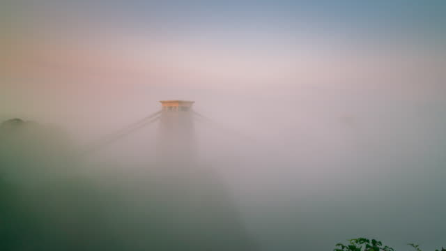 clifton suspension bridge in bristol under morning fog, england, 4k time-lapse - bristol england stock videos & royalty-free footage
