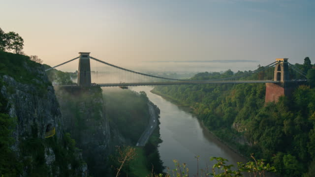 clifton suspension bridge in city of bristol, south west england at sunrise with fog, 4k time-lapse - bristol england stock videos & royalty-free footage