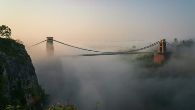 clifton suspension bridge over river avon in bristol, south west england at sunrise with fog, 4k time-lapse - bristol england stock videos & royalty-free footage