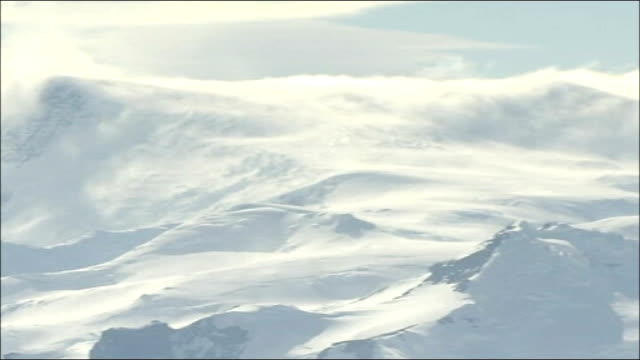 'big melt': threat to wildlife in antarctica; antarctica: ext good general view snow covered mountains with peaks covered in clouds clouds passing... - report produced segment stock videos & royalty-free footage