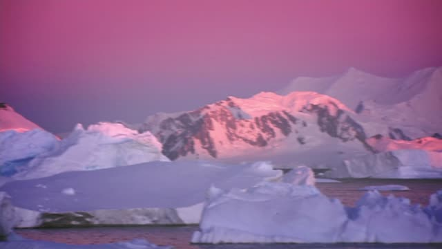 scientific ways to meet global temperature target r04020809 / icebergs and snow covered mountains under pink sky - iceberg ice formation stock videos & royalty-free footage
