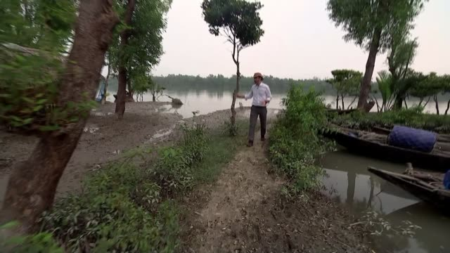 Climate change effects / Country becomes target for Isis BANGLADESH river as along in boat and trees and riverside dwellings seen from moving boat...