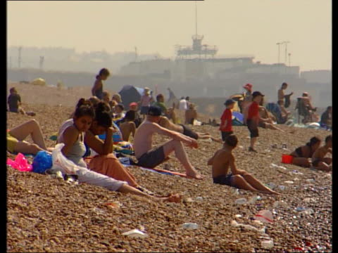 climate change in britain; meridian tv - no resale england: sussex: brighton: ext/sunny side woman and girl sitting on shingle beach beside sea gv... - deck chair stock videos & royalty-free footage