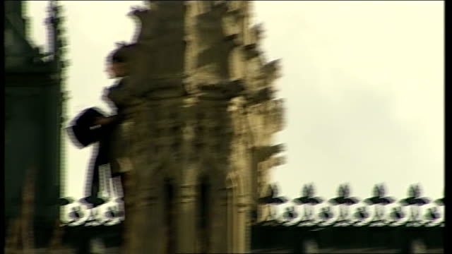 Climate change protest on top of Houses of Parliament Demonstrators along roof accompanied by security officers and waving then climbing up...