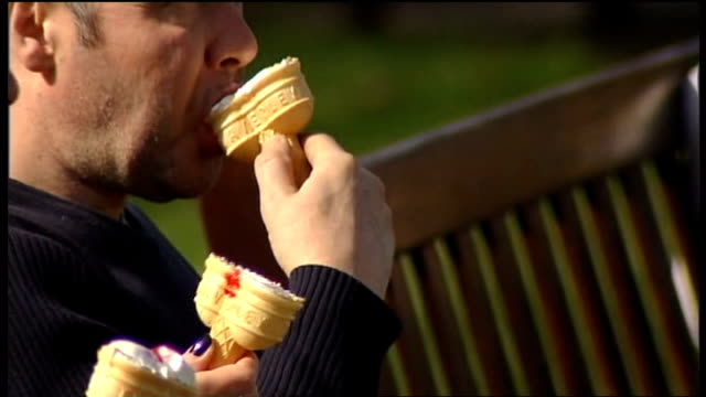 climate change warning as freezing conditions continue 2832012 / people sitting in park in sunshine sunbathing ice cream eaten people in park some... - eaten stock videos & royalty-free footage