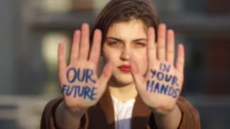 Climatic strike. Close portrait of a short-haired girl. The student holds her hands in front of her, the inscription on them - our future is in your hands