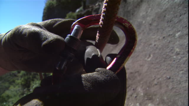 a climber affixes carabiners to a rappelling rope. - カラビナ点の映像素材/bロール