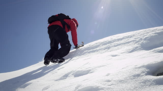 climber arrives at the snow-covered mountain peak - mountain peak stock videos and b-roll footage