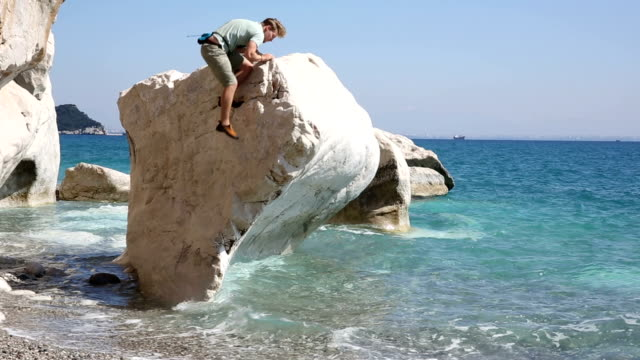 climber ascends boulder in sea shallows - mediterranean turkey stock videos and b-roll footage