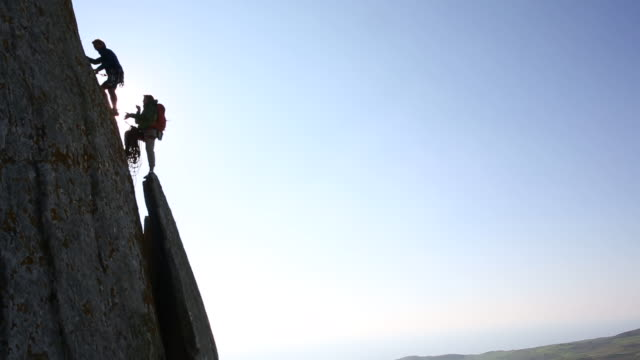 climber ascends sheer rock face while teammate belays - corda video stock e b–roll