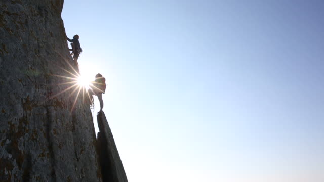 Climber ascends sheer rock face while teammate belays