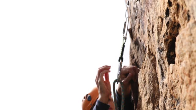climber ascends steep cliff above sea - sports helmet stock videos & royalty-free footage