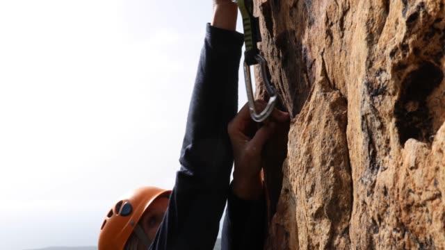 vídeos de stock, filmes e b-roll de alpinista sobe íngreme penhasco acima do mar - roldana