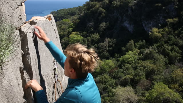 Climber ascends steep rock above hills sea, clips anchor