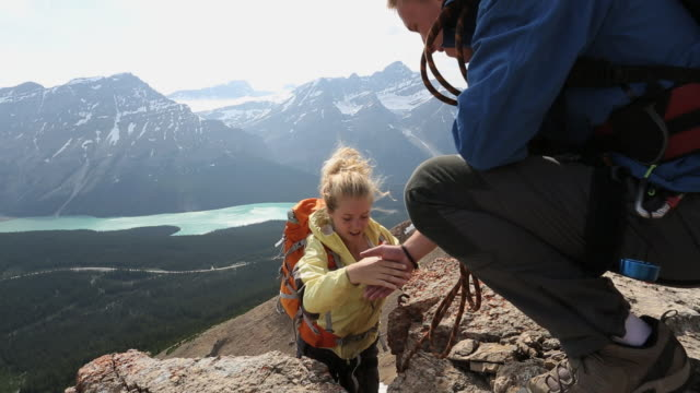 climber assists teammate while climbing rock above mtns - tilt stock videos & royalty-free footage