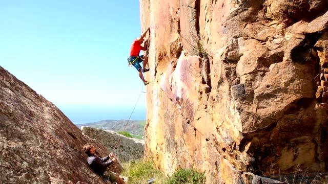 kletterer wetter in exponierten lagen optimal verstauen mitspieler auf steilen klippe über dem meer - felsklettern stock-videos und b-roll-filmmaterial