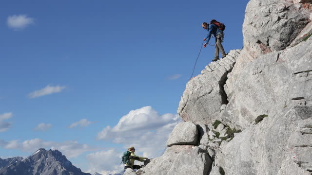 climber belays teammate while climbing ridge above mtns - belaying stock videos & royalty-free footage