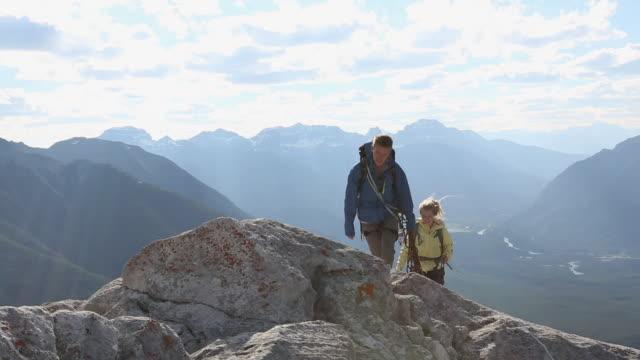 climber couple approach mtn summit, exchange hugs - 最上部点の映像素材/bロール