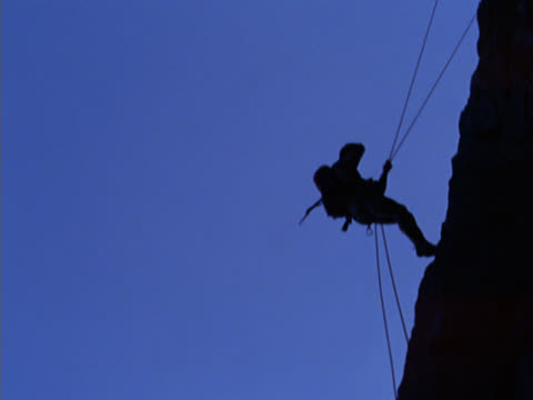 Climber descending cliff on mountain