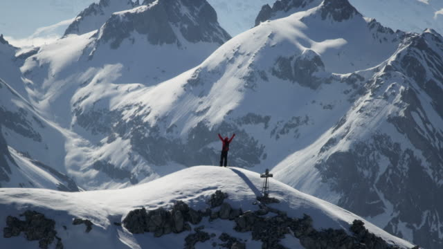 stockvideo's en b-roll-footage met climber exultant on a snow-covered mountain peak - exploratie