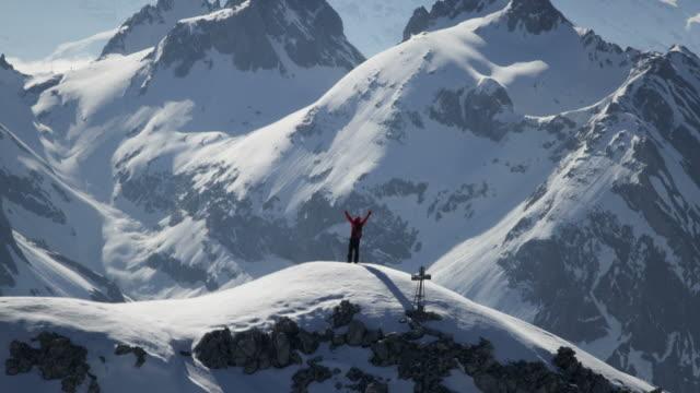 kletterer exultant auf einem schneebedeckten berggipfel - abenteuer stock-videos und b-roll-filmmaterial