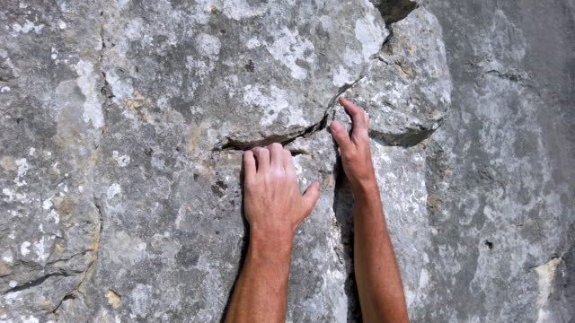 climber gripping crevice in der felswand - free climbing stock-videos und b-roll-filmmaterial