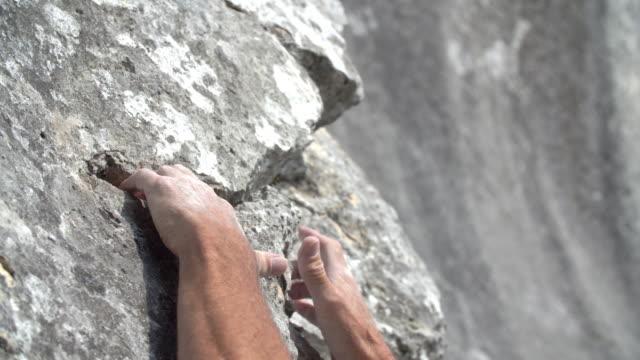 stockvideo's en b-roll-footage met klimmer die spleet in het gezicht van de rots grijpt - crevice