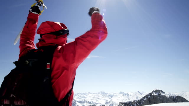 Climber is cheering on a mountain peak
