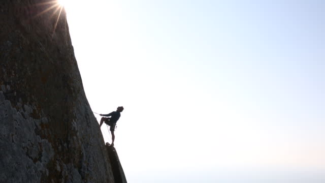 climber looks off to view from high perch on rock face - rock face stock videos & royalty-free footage