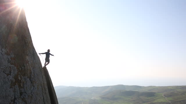 stockvideo's en b-roll-footage met climber looks off to view from high perch on rock face - moed