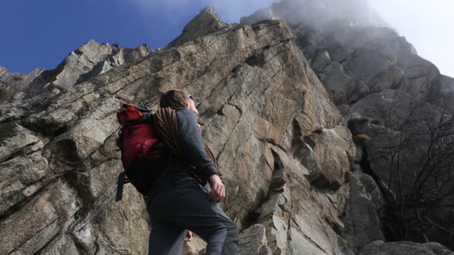 climber looks overhead as fog enshrouds rock crest - looking up stock videos & royalty-free footage