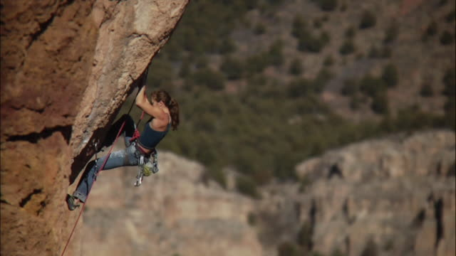 ws tu ts climber makes few difficult moves on steep rock face then falls off and rope catches her / canon city / shelf road,co,usa - rock face stock videos & royalty-free footage