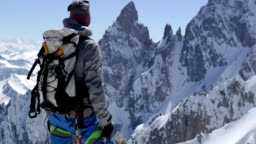 Climber mountaineer man reaching snowy mount top with ice axe in sunny day.Mountaineering ski activity. Skier people winter snow sport in alpine mountain outdoor.Back view.Slow motion 60p FullHD video