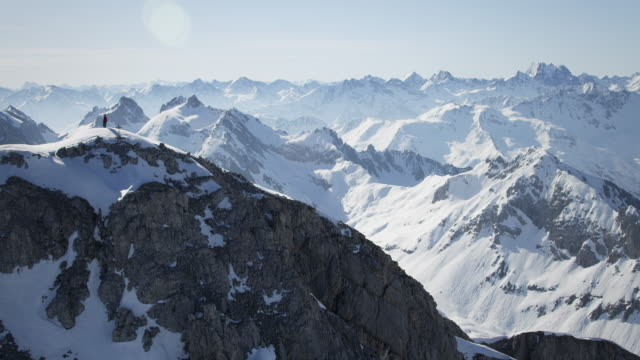 climber on a snow-covered mountain peak - mountain peak stock videos and b-roll footage