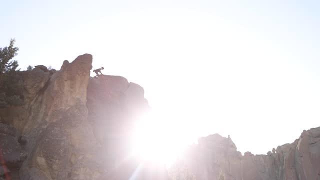 vídeos de stock e filmes b-roll de climber on top of rock face with sun flare in smith rock - outdoor pursuit