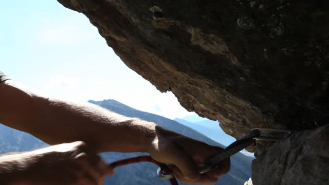 vídeos de stock e filmes b-roll de climber places gear, then climbs overhanging rock above - equipamento de alpinismo