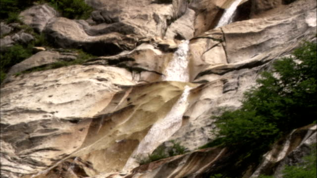 a climber rappels down a rock face next to a waterfall. - rock face stock videos & royalty-free footage