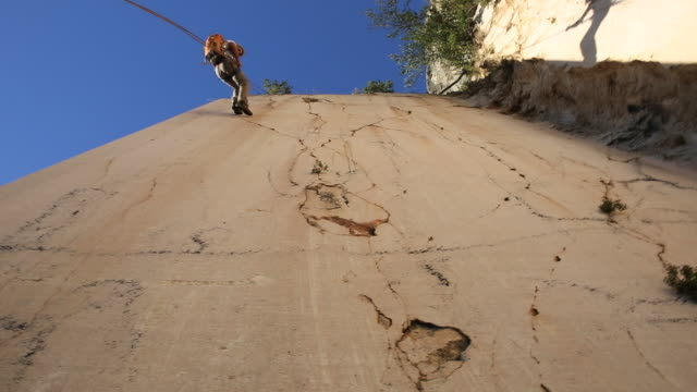 climber rappels down marble cliff face - abseiling stock videos & royalty-free footage
