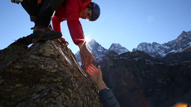 vidéos et rushes de climber reaches pinnacle summit, extends hand for companion - atteindre
