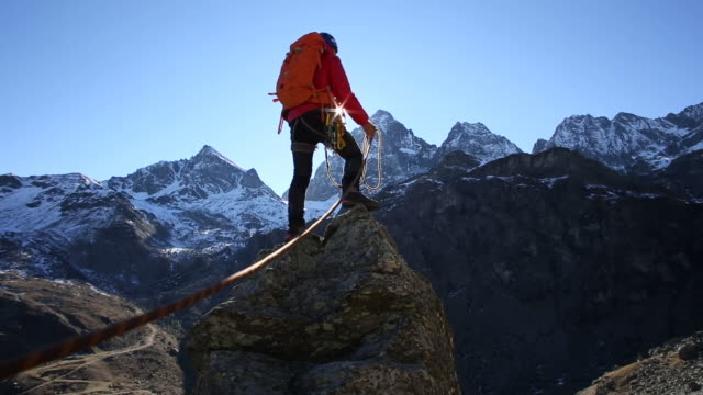 Climber reaches pinnacle summit, spreads arms wide