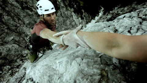 stockvideo's en b-roll-footage met hd: climber reaching for a helping hand - moving up